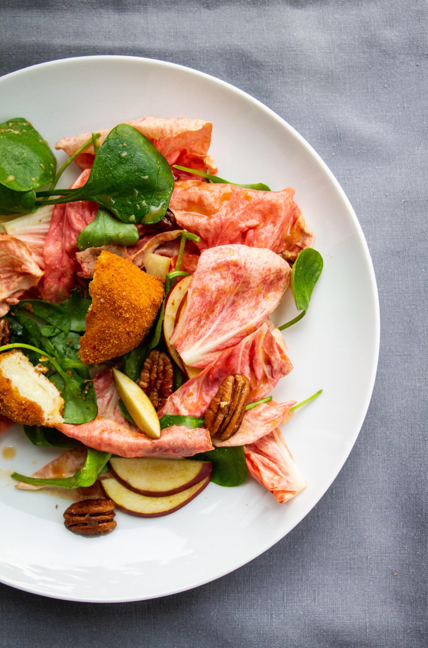 GEbackene Ziegencamembert Ecken auf rosa Radicchio-Salat angerichtet