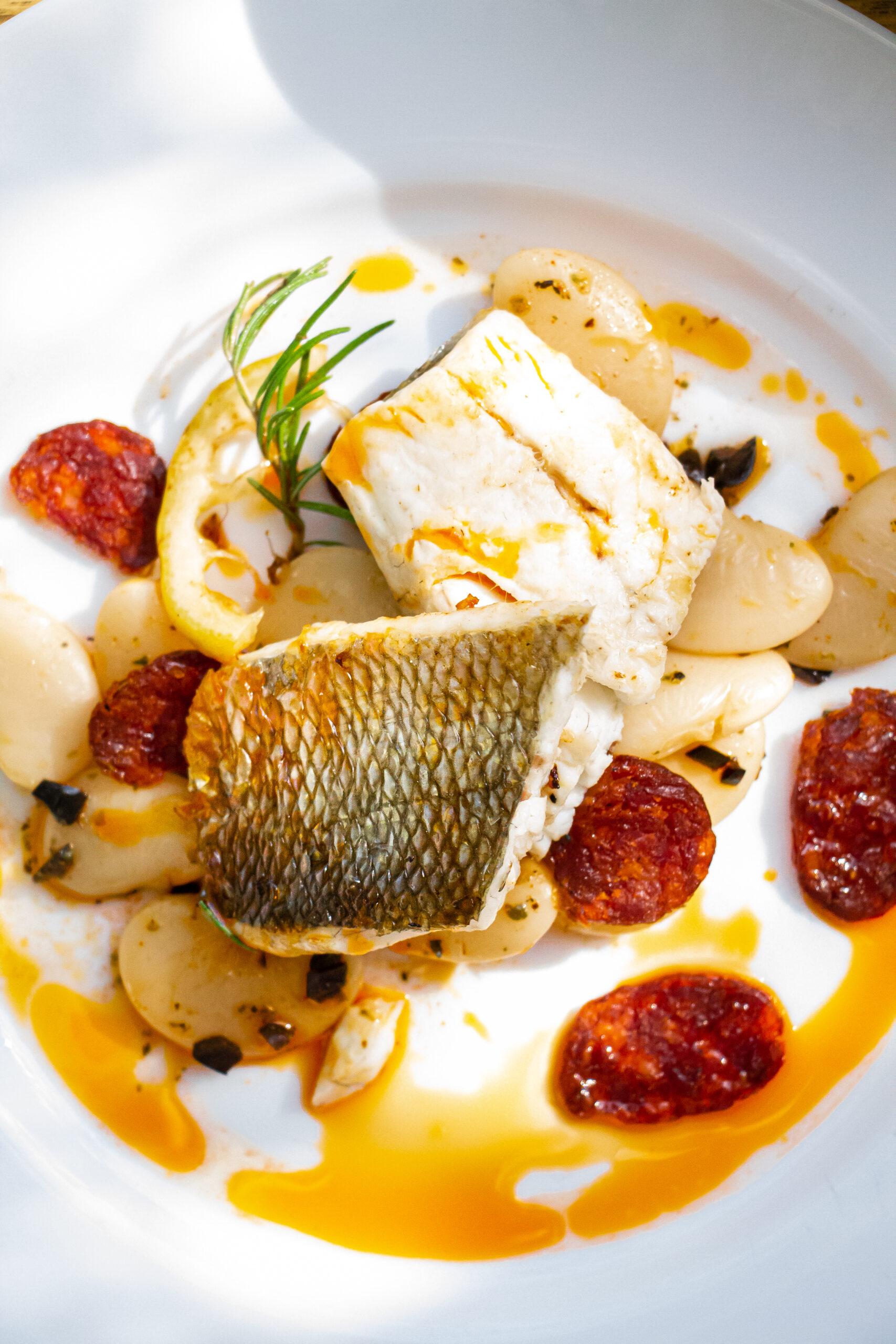 Bohnensalat mit Fischfilet und Chorizo, auf Teller angerichtet
